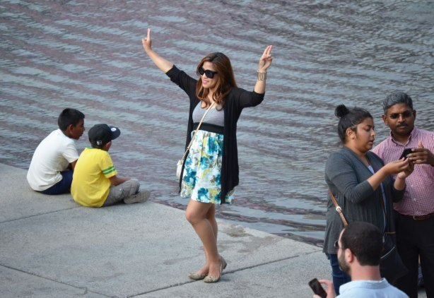 Three sets of photos taken beside water.  Two boys are sitting crossed legged right at the edge.  A young woman is posing with her hands in the air and her fingers in peace sign.  A south Asian couple are looking at a picture that they have taken on a smartphone.