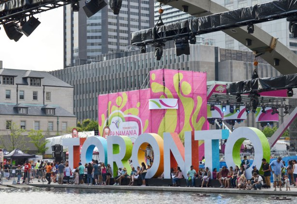 A view of the 3D Toronto sign from the southeast corner of Nathan Phillips Square showing the lights on the arches above the water as well as the Panamania pink and yellow covering on the lights and sound system for the stage.
