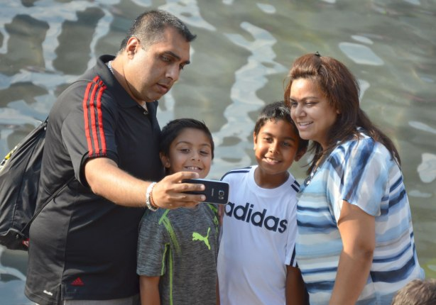 A family of four, mother, father and two sons, are taking a selfie.