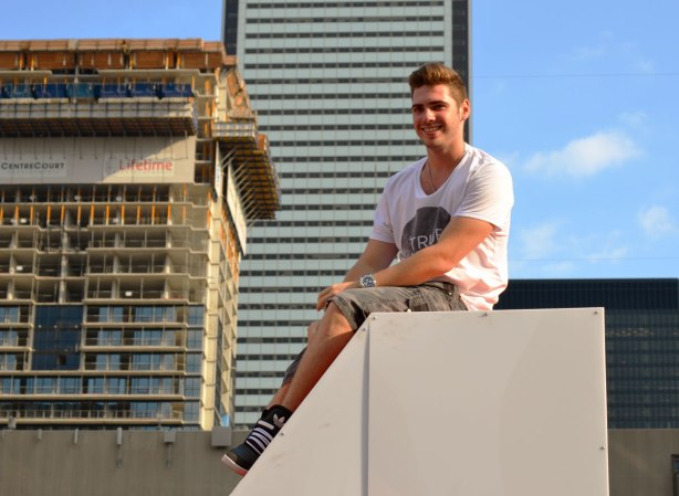 A young man has climbed up the side of the N in the Toronto sign as is sitting on top of it.