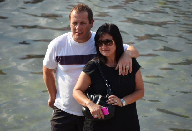 A couple poses beside the water in Nathan Phillips Square.