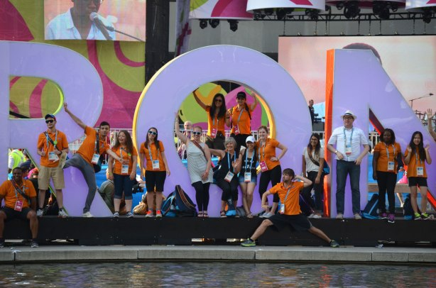 A group of Pan Am games volunteers in their orange T shirts pose in front of the 3D Toronto sign.