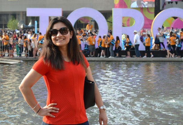 A woman with long brown hair and wearing a red T shirt poses beside the water.  The 3D Toronto sign is in the background on the other side of the pool.