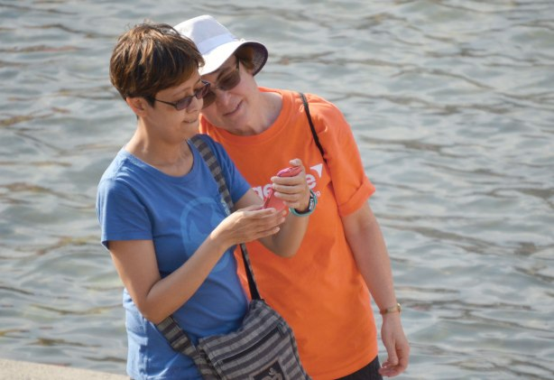 Two women check a picture on a smartphone.  They have just taken a selfie.