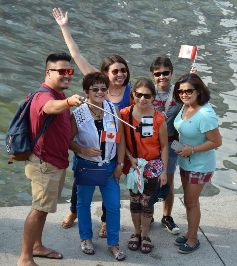 Six people, a man and five women, are talking a selfie with a phone on a selfie stick.  Two of the women have small Canadian flags.  Another woman has her arm up in the air.