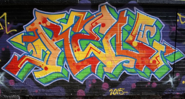 tag in reds, oranges and yellows, on green, with dark blue background