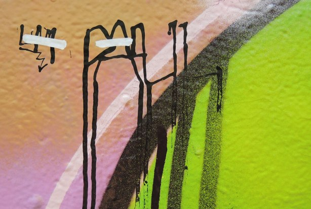 close up of a street art painting that now looks abstract, black lines on green, pink and beige
