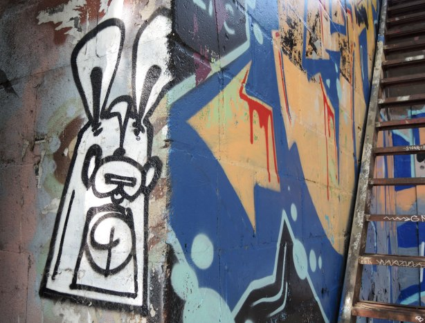 a black and white poser bunny on a wall at the corner, around the corner is a painted arrow that is part of a graffiti painting