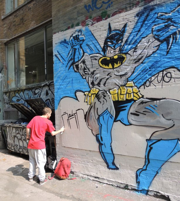 A young man is spray painting part of a batman mural.  The figure of batman is completed and is about 4 meters tall.  A city scene is being added in the bottom corner