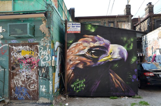 A large bird head street art painting covers the end of a building in a lane