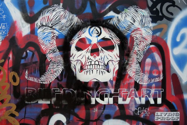 A white graffiti skull with the words belleding heart written underneath