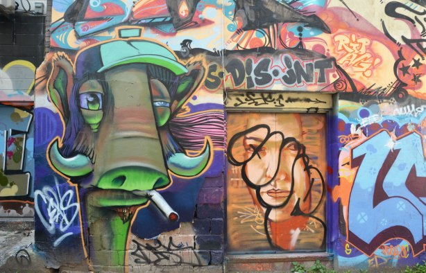 A stylized greenish brown bull with horns is smoking a cigarette, only the head is shown.  It is on a wall and beside it is a door that had a woman's face painted on it.  The face has been tagged over.   Dis jnt is written across the top of the door.  disjoint perhaps.