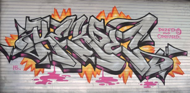 tag in silver and black with pink and orange highlights on a grey metal door