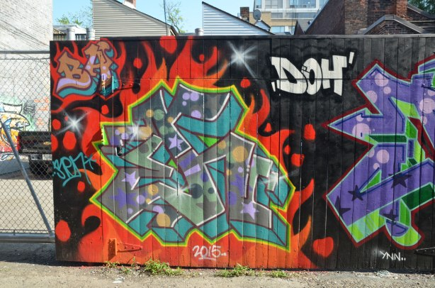 tags on a black wall in an alley.  Between them is the word doh