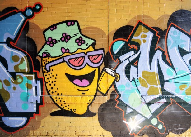 graffiti picture of a lemon wearing sunglasses and a sun hat and holding a glass of lemonade