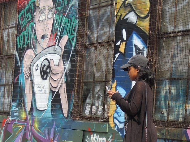 Woman taking picture on a smartphone, standing beside a street art piece of a man with earphones plugged into