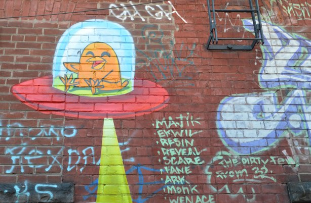 uber 5000 birdie in a little space ship with a beam of light eminating from the bottom, on a red brick wall