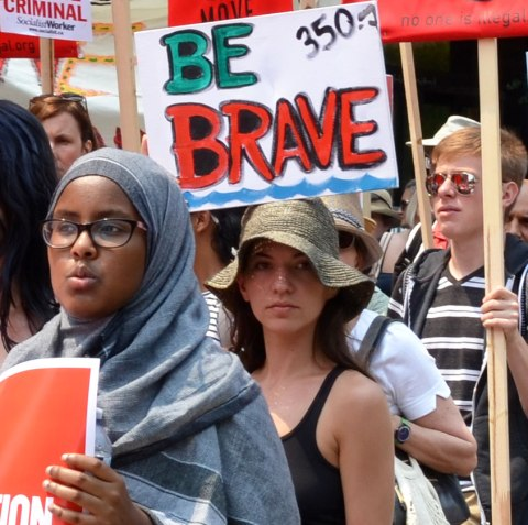 jobs, justice and climate action protest march  - a young woman in a head scarf holds a red and white sign, the woman behind her is wearing a floppy hat and there is a sign that says Be Brave in large capital letters above her head.