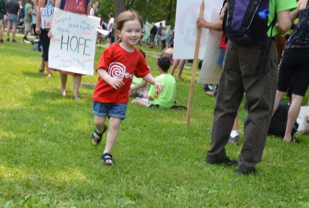 A young girl in a bright red Tshirt runs in front of some protesters, one of whom is holding a sign that says Hope.