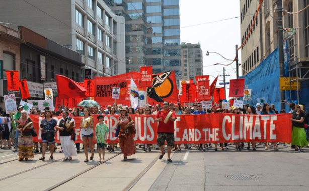 jobs, justice and climate action protest march - the lead banner of the march.  It says Jobs, Justice and the Climate. It is red with white letters and is almost the full width of the street.  A few drummers and dancers are in front of the banner.  Many people with signs and flags are behind the banner.