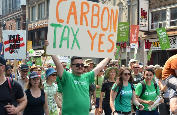 A man wearing a green party T-shirt is carry a large sign that says 'carbon tax yes'.  There are other green party supporters with him as they walk in a protest march in Toronto