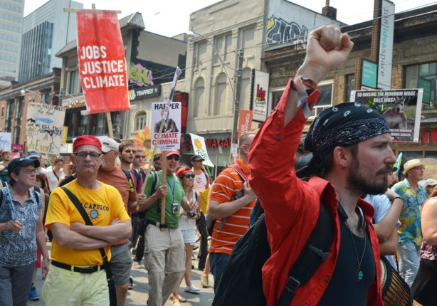A man in a red shirt pumps his fist in the air as he walks in a protest march