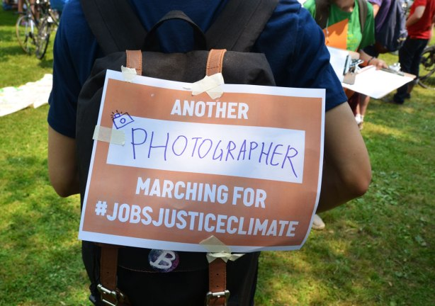 A person wearing a sign that says 'Another photographer marching for #jobsjusticeclimate on his back.