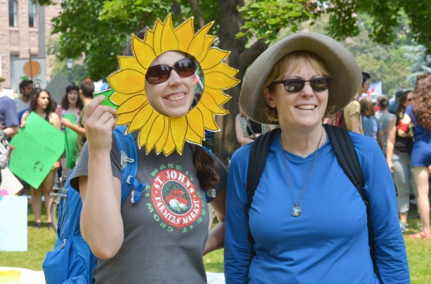 At a protest rally, two women are posing for a picture.  One has a large cut out around her face that makes her face look like a large yellow flower