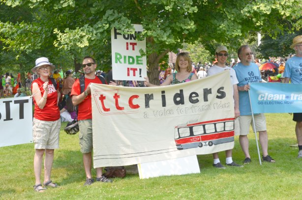 At the jobs, justice and climate action protest rally, four people hold a banner that says 'TTC riders, a voice for ttc riders' and it has a picture of a street car on it as well.