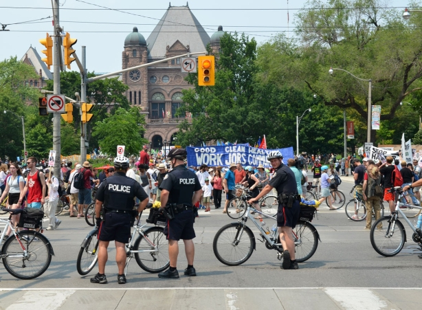 policemen on bikes block the street as they direct a march through city streets