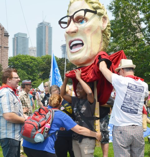 A couple of people are helping a woman prepare to wear a large effigy.  A very large head of a woman wearing dark rimmed glasses.