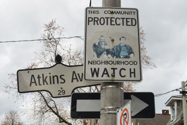 Neighbourhood watch sign by Atkins Ave.., picture of Mel Gibson and Danny Glover has been pasted on it, two actors from Lethal Weapons movies.