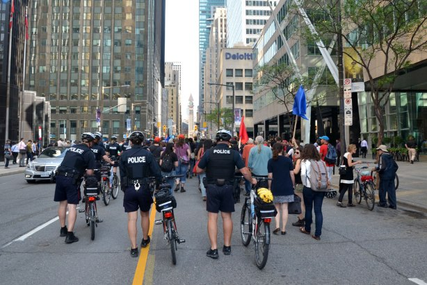 riseupTO demonstration and march - a line of policemen walk their bikes behind a group of protesters as they walk up Bay St. in downtown Toronto, with the clock tower of old city hall in the backbround.