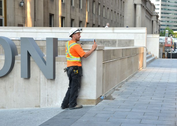 A construction worker in yellow & Orange work clothes and hard hat, stops work to take a photo of a passing demonstration in front of Union Station.