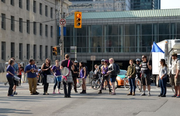 riseupTO demonstration and march - a group of young people drumming as they stand in a line in the middle of an intersection blocking traffic
