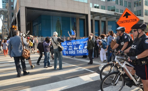 riseupTO demonstration and march - a group of photographers stand in front of marchers with a blue banner that reads