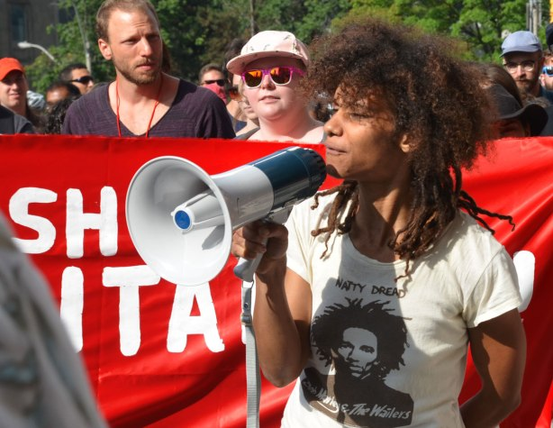 a young woman with afro black hair and wearing a Bob Marley T-shirts is speaking through a megaphone at a protest march.   She is standing in front of a red and white banner that is being held up by a few other people