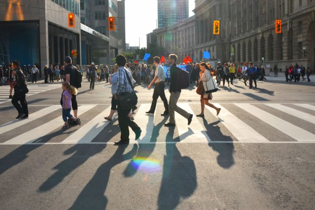 riseupTO demonstration and march - pedestrians cross a street with the morning sun low in the sky so the people cast long shadows towards the camera.  A group of protesters is in the background.