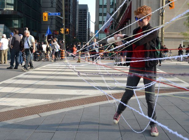 a woman is unravelling a skein of yarn and is using it to make a barrier across a city street.  She is using two hydro poles to wrap the yarn around.
