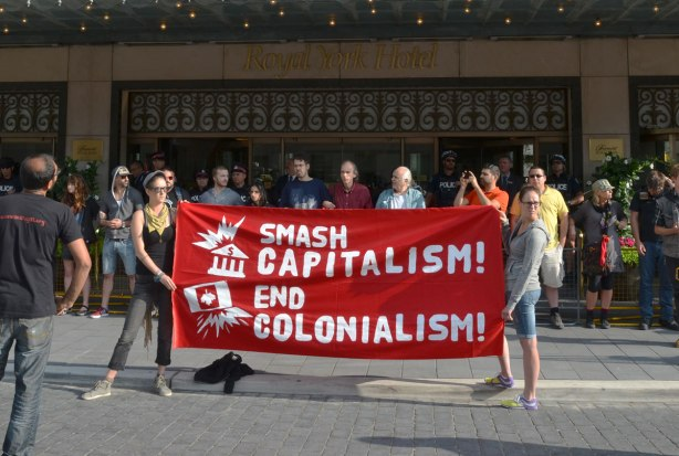 riseupTO demonstration and march - two woman holding a red banner that reads 'Smash Capitalism End Colonialism'  They are standing in front of a line of peeople arm in arm infront of the Royal York Hotel front entrance.  Some police are between the protesters and the door.
