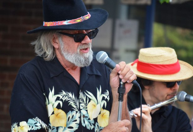 lead singer for Blue Room, grey hair and beard, Hawaiian shirt, black hat, singing at streetfest at the beach