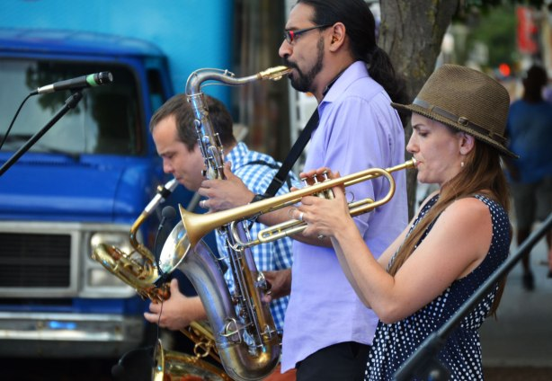 Three brass players performing outside.  Two men on saxophones and a woman playing a trumpet