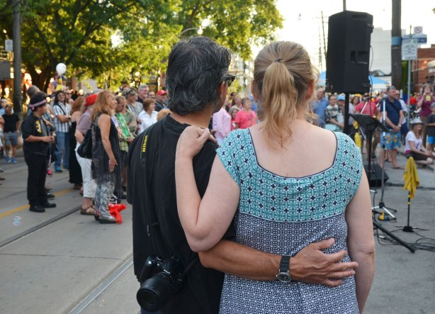 A man has his arm around a woman's back and her hand is on his shoulder as they watch a musical performance outside along with a number of other people