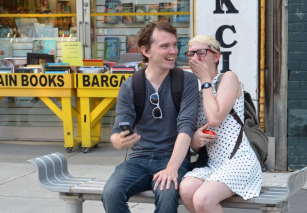 A couple sitting a bench laughing.  They were taking a selfie when they noticed 4 photographers taking their picture.  She is embarrassed and is covering her face, he is laughing.