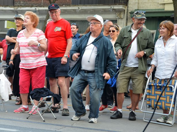 a group of older people dancing to the music on the street at a street music festival