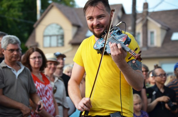 Dr. Draw playing his violin in front of a crowd, outdoor street music festival