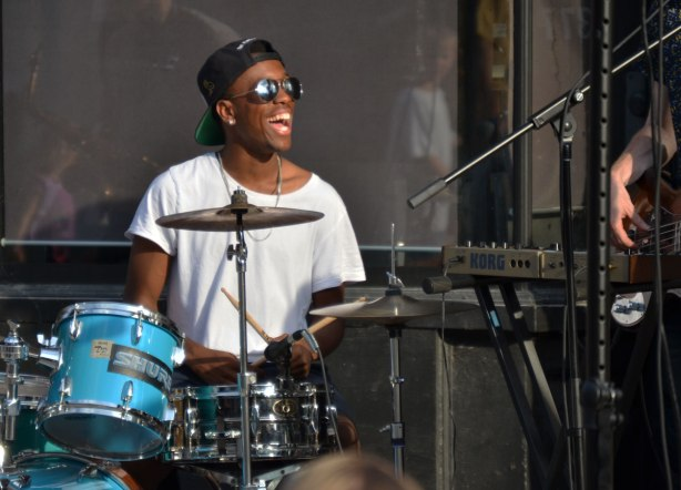 young black man, drummer, laughing as he plays the drums