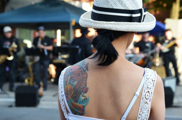 A woman's back is to the camera as she watches live music outside.  Her black hair is tied in a short ponytail, she is wearing a white hat and a white sundress.  She has a large tattoo on one shoulder blade.