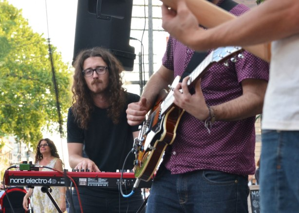 keyboard player in Conor Gains band playing at Streetfest at the Beach, Queen St. in Toronto in July, summer evening