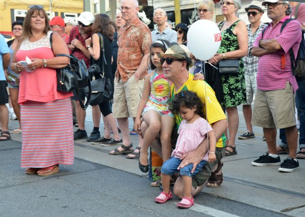 A man is squatting on the sidewalk with two girls on his knee.  Both girls have balloons.  They are part of a crowd watching a band perform in a street music festival
